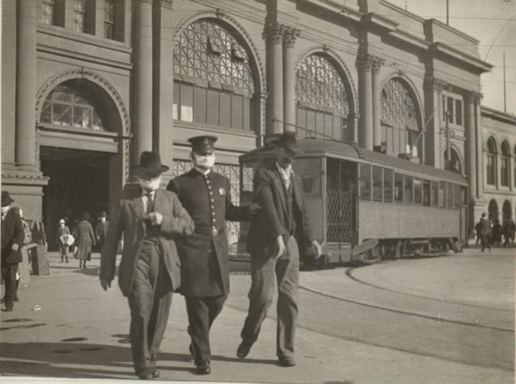 Policeman with flu mask leading two men away from the Ferry Building