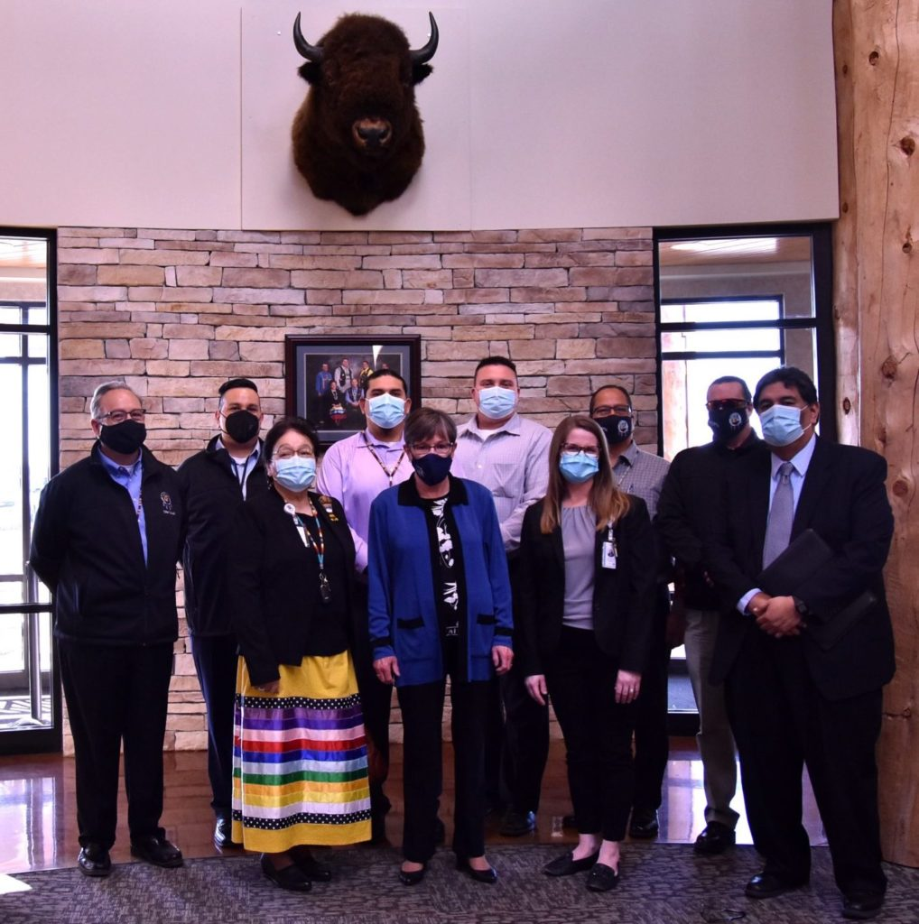 Image of Prairie Band Health Center Staff and Gov. Laura Kelly standing in the Health Center under a Bison head mount.