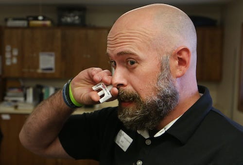 Image of Seth Dewey, Reno County Health Department's Substance Misuse Health Educator, holding Narcan nasal spray to his nose. He is demonstrating how Narcan nasal spray is administered to a person who has overdosed.