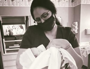 Image of a woman in a mask holding an infant swaddled in a blanket.